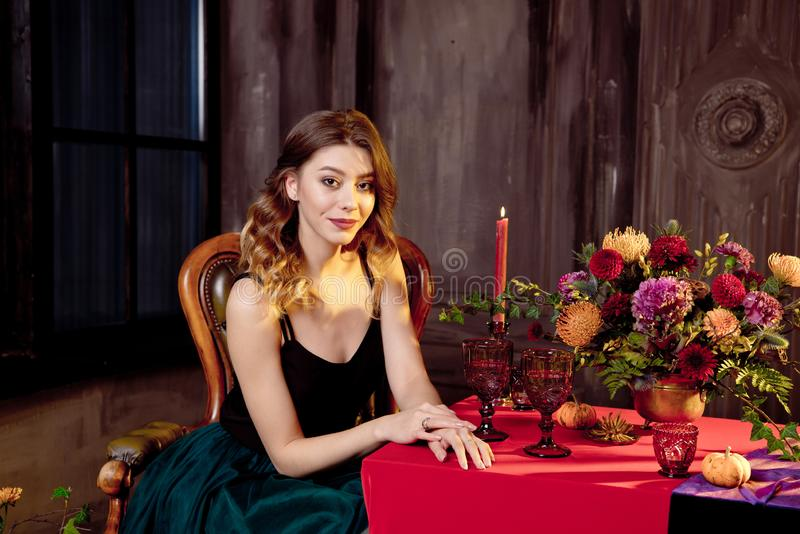 Happy Halloween.Attractive young woman getting ready for Halloween by setting the table for a festive dinner. Beautiful. Woman pumpkin stock image