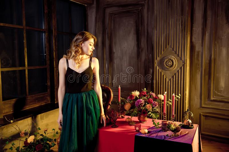 Happy Halloween.Attractive young woman getting ready for Halloween by setting the table for a festive dinner. Beautiful. Woman pumpkin royalty free stock photos