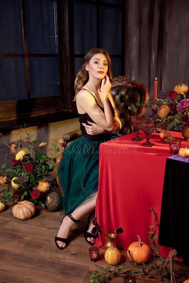 Happy Halloween.Attractive young woman getting ready for Halloween by setting the table for a festive dinner. Beautiful. Woman pumpkin stock photography