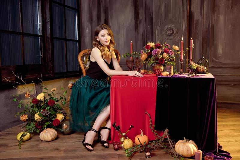 Happy Halloween.Attractive young woman getting ready for Halloween by setting the table for a festive dinner. Beautiful. Woman pumpkin royalty free stock images