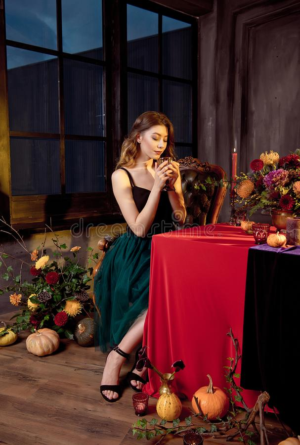 Happy Halloween.Attractive young woman getting ready for Halloween by setting the table for a festive dinner. Beautiful. Woman pumpkin royalty free stock image