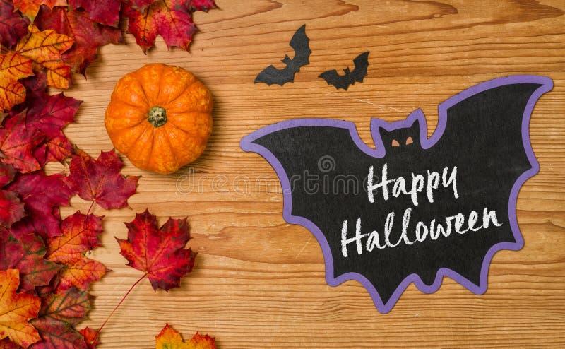 Happy Halloween. Autumn foliage with a pumpkin and a blackboard - Happy Halloween royalty free stock photo