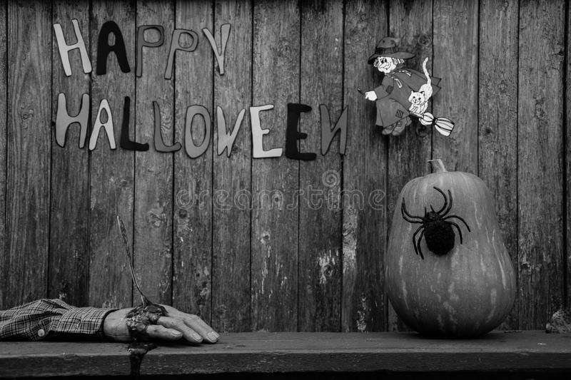 Happy Halloween background. Black and white Jack pumpkin head with spider, witch, severed hand and an inscription on a wooden background Happy Halloween royalty free stock photography