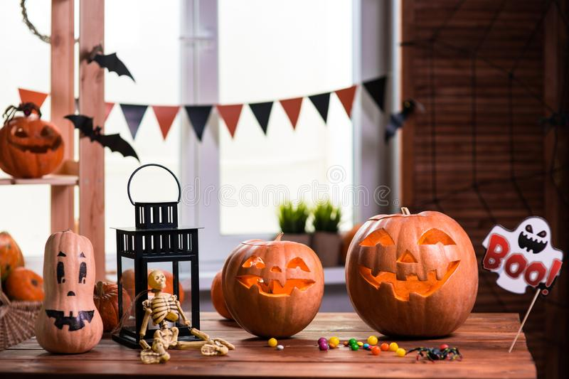 Happy Halloween. Background in front of a window with pumpkins,. Lantern, spiders and other symbols of a terrible holiday royalty free stock photography