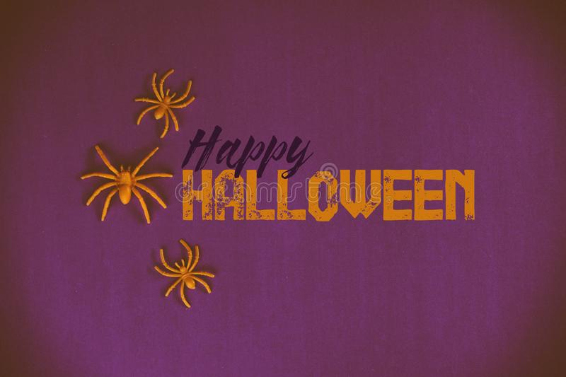 Happy Halloween graphic text. Happy Halloween banner with text and orange spiders by holiday text with purple background royalty free stock photography