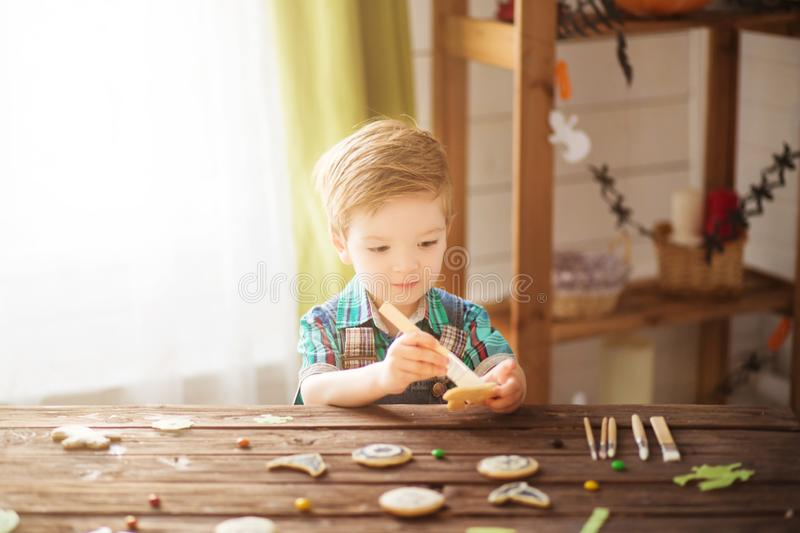Happy Halloween. Beautiful happy little preschool kid boy covering cookies for Halloween cookies at home. Child celebrating tradit royalty free stock photo