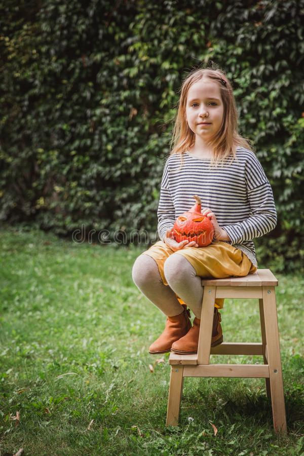 Happy Halloween. Beautiful smiling toddler seats on wooden chair and holds little pumpkin Jack OLanterns outdoors royalty free stock images