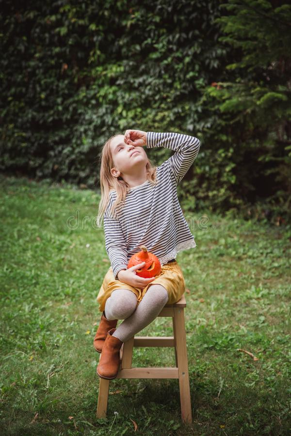 Happy Halloween. Beautiful smiling toddler seats on wooden chair and looks through her fingers like a pair of binoculars, holds li. Ttle pumpkin Jack O Lanterns stock photos