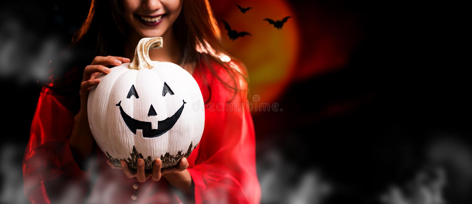 Happy Halloween. Beautiful woman costume and holding pumpkin. Copy space on dark background stock images