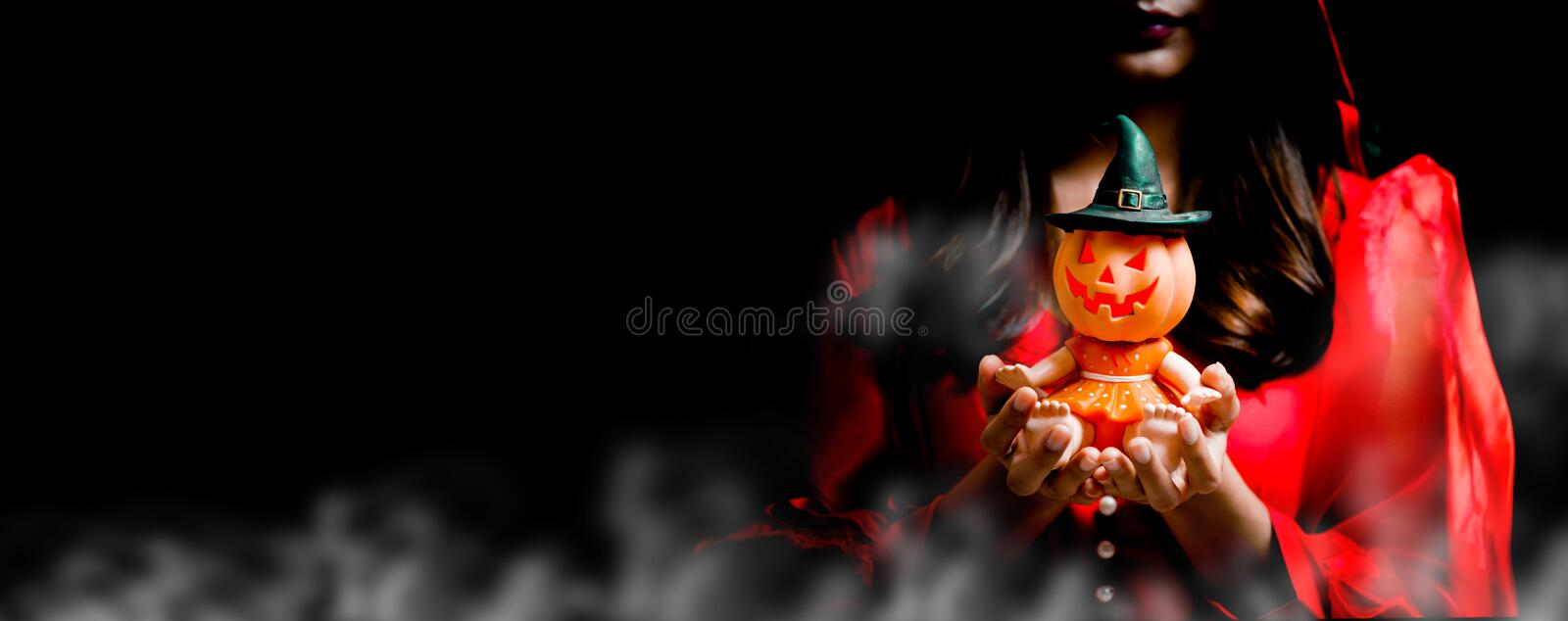 Happy Halloween with pumpkin, trick or treat in autumn season. Happy Halloween. Beautiful woman costume and holding pumpkin toy. Copy space on black background royalty free stock photo