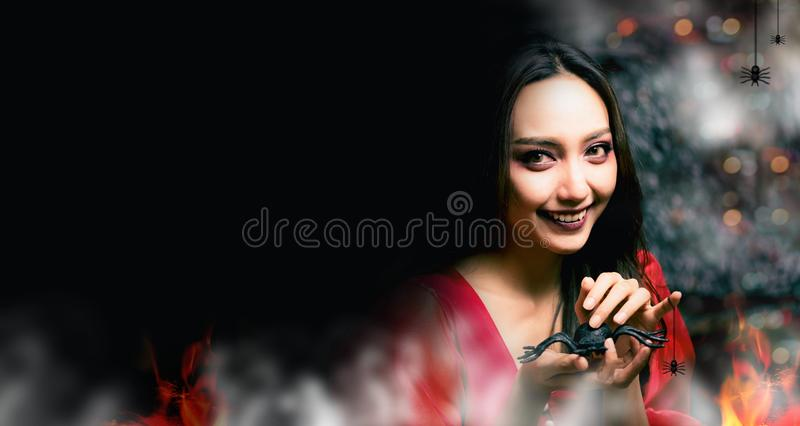 Happy Halloween. Beautiful woman costume and holding spider. Copy space on dark background royalty free stock photo