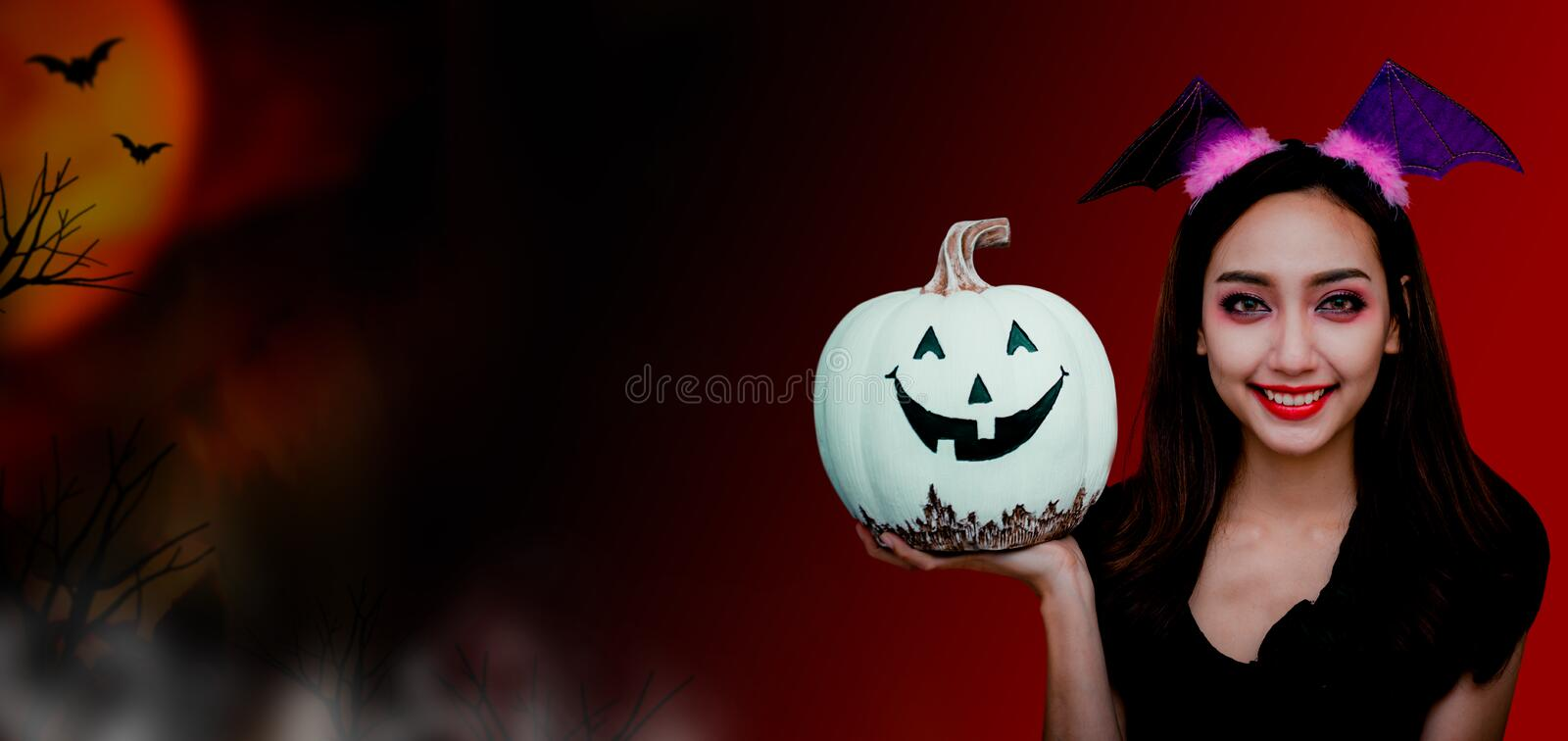 Happy Halloween concept. Happy Halloween. Beautiful woman costume and holding white pumpkin. Copy space on dark background royalty free stock photos