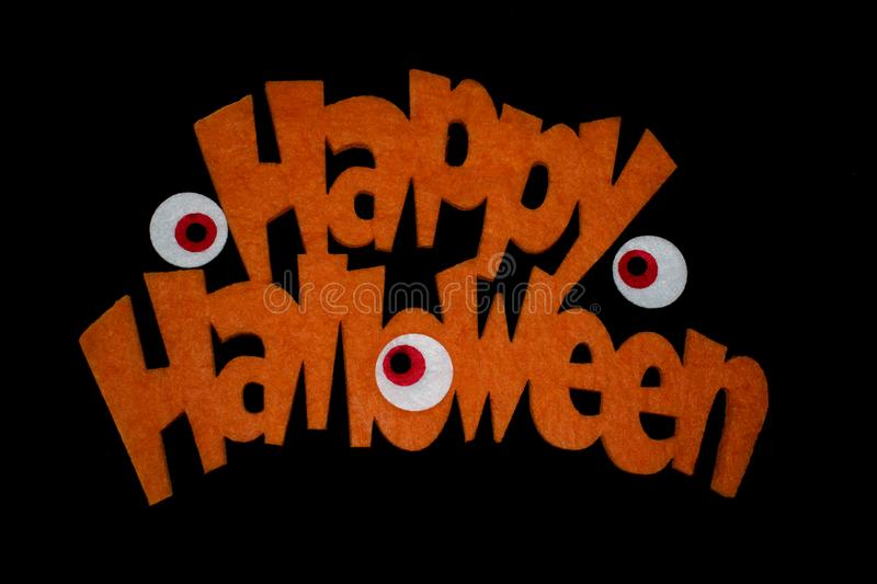 Happy Halloween on black backgound. Happy halloween in orange letters on a black background and some scary eyes royalty free stock images