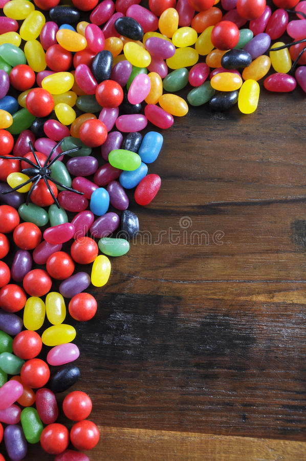 Happy Halloween candy background with spiders on rustic dark wood background stock image