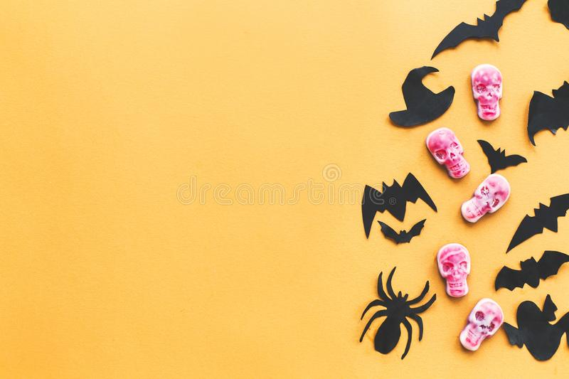Happy Halloween.  Halloween candy border with skulls, black bats, ghost, spider paper decorations on yellow background. Copy space. Trick or treat concept royalty free stock photo