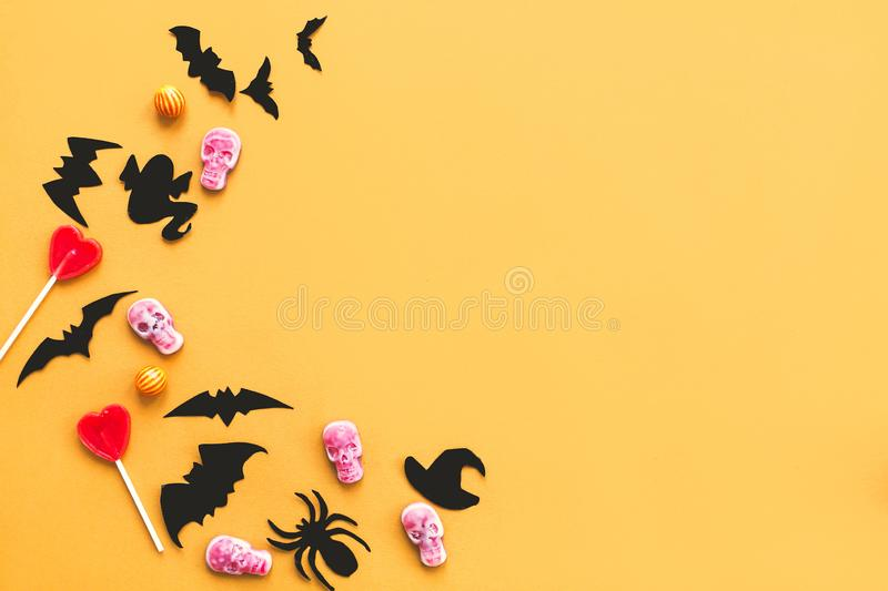 Happy Halloween.  Halloween candy border with skulls, black bats, ghost, spider paper decorations on yellow background. Copy space. Trick or treat concept stock photos