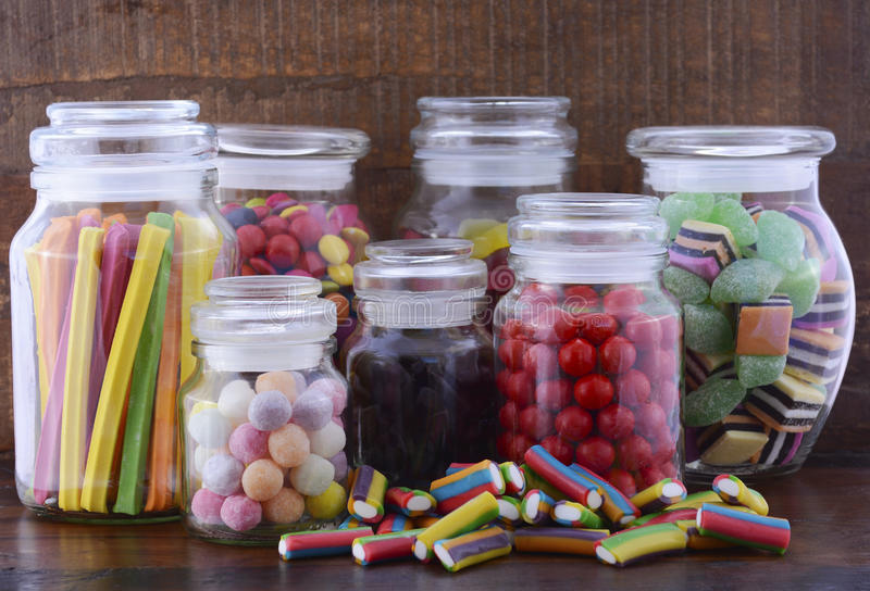 Happy Halloween Candy in Glass Apothecary Jars. On dark wood table royalty free stock photos