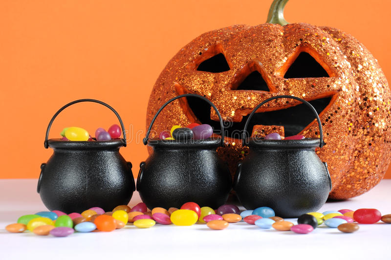 Happy Halloween candy in trick or treat carry cauldrons with pumpkin. On orange background stock images