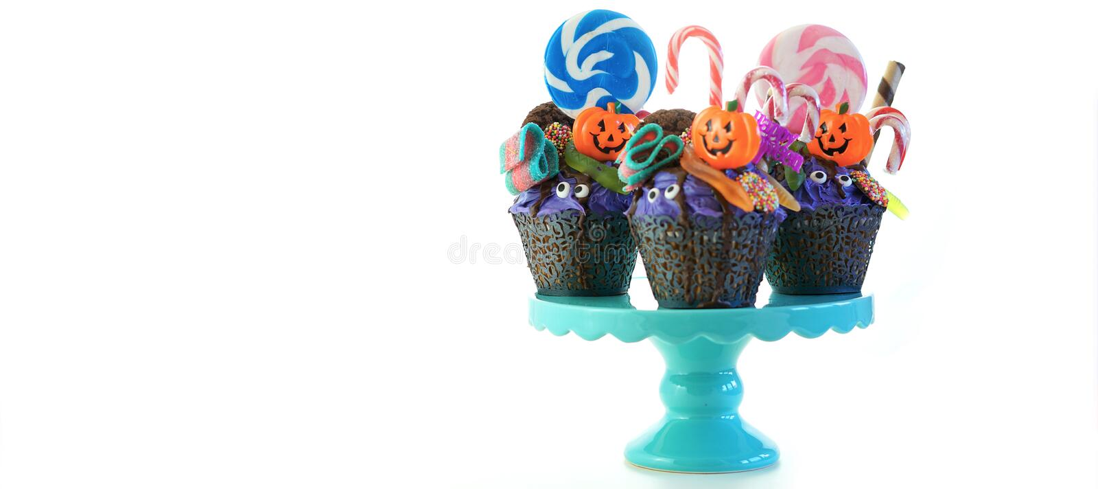 Halloween candyland drip cake style cupcakes with lollipops and candy on white. royalty free stock images