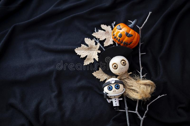 Happy Halloween card concept. Cute wooden witch and doctor doll with funny pumpkin on black fabric texture background royalty free stock image
