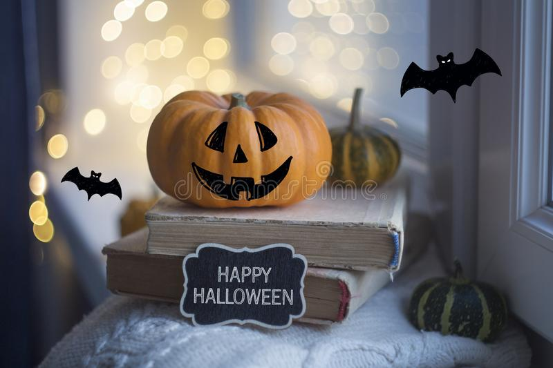 Happy Halloween card. Halloween pumpkins and old books are on a windowsill royalty free stock photos
