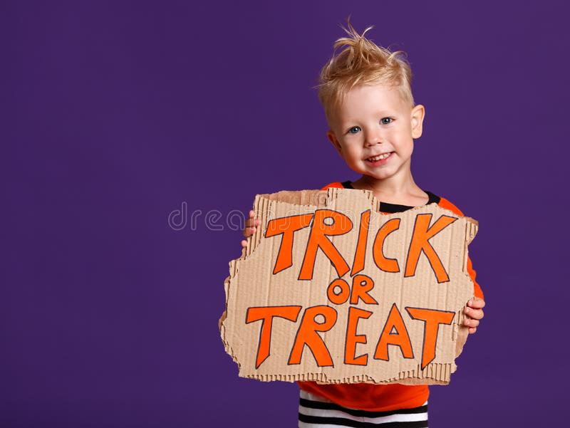 Happy Halloween! cheerful child boy in costume with pumpkins on. A violet purple background stock images