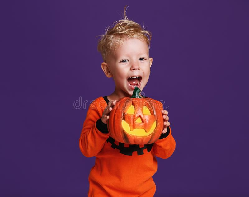 Happy Halloween! cheerful child boy in costume with pumpkins on. A violet purple background stock image