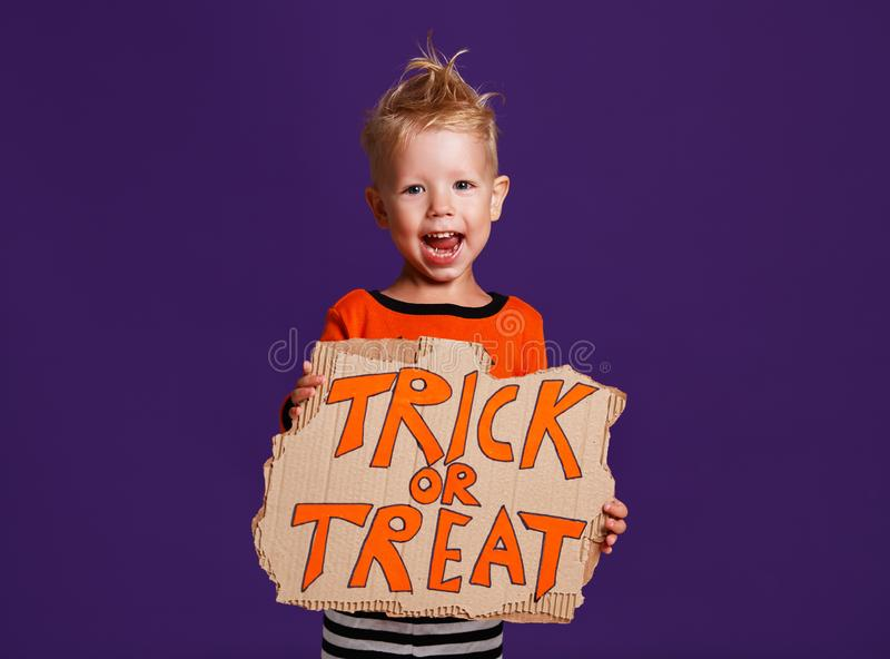 Happy Halloween! cheerful child boy in costume with pumpkins on. A violet purple background royalty free stock image