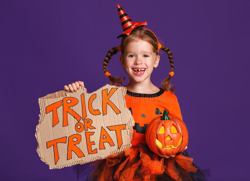 Happy Halloween! cheerful child girl in costume with pumpkins on. A violet purple background royalty free stock photos