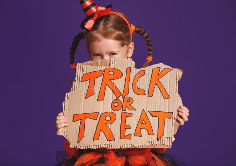 Happy Halloween! cheerful child girl in costume with pumpkins on. A violet purple background royalty free stock images