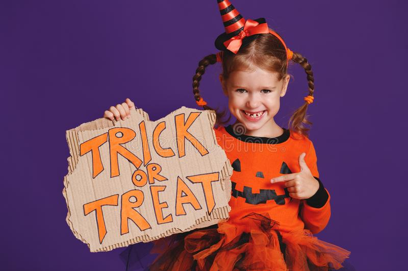 Happy Halloween! cheerful child girl in costume with pumpkins on. A violet purple background royalty free stock photo