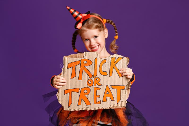 Happy Halloween! cheerful child girl in costume with pumpkins on violet purple background stock photo
