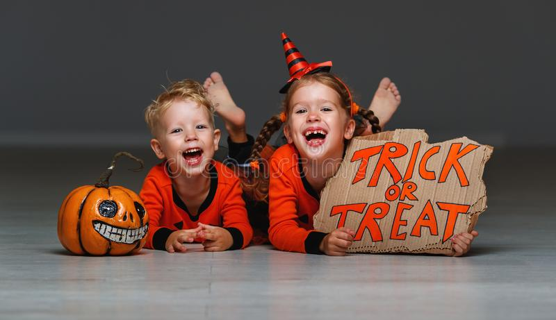 Happy Halloween! cheerful children in costume with pumpkins on g. Happy Halloween! cheerful children in costume with pumpkins on a grey background royalty free stock images