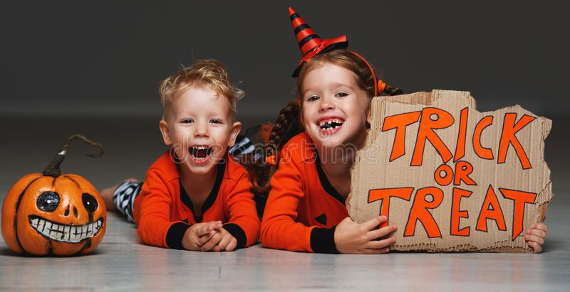 Happy Halloween! cheerful children in costume with pumpkins on g. Happy Halloween! cheerful children in costume with pumpkins on a grey background stock photography