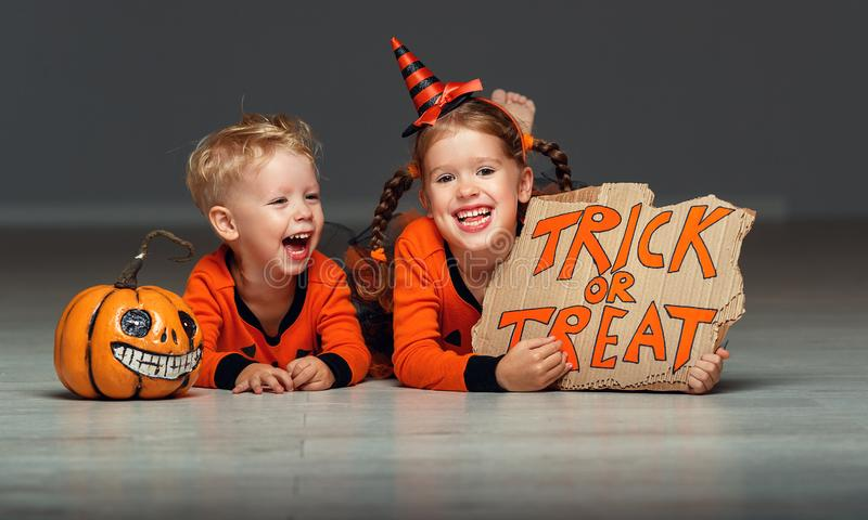 Happy Halloween! cheerful children in costume with pumpkins on grey background stock image