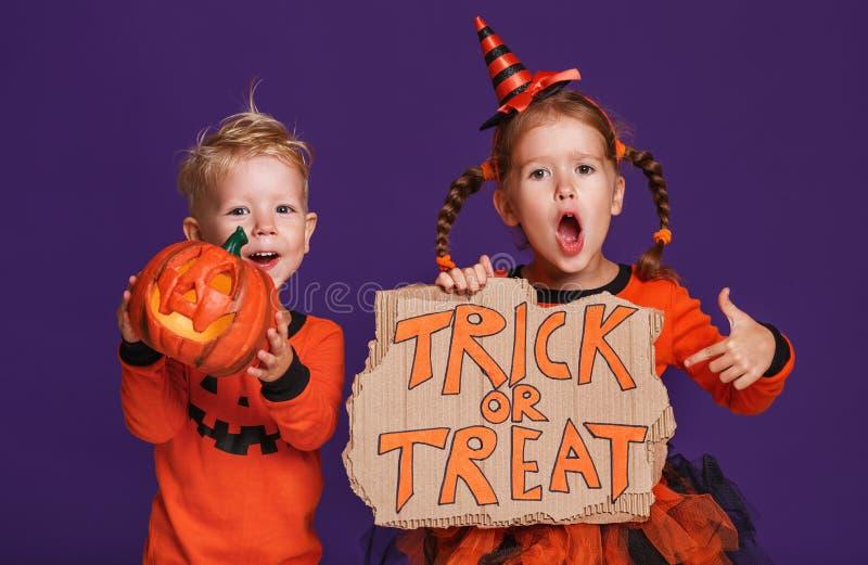 Happy Halloween! cheerful children in costume with pumpkins on v. Happy Halloween! cheerful children in costume with pumpkins on a violet purple background royalty free stock photos