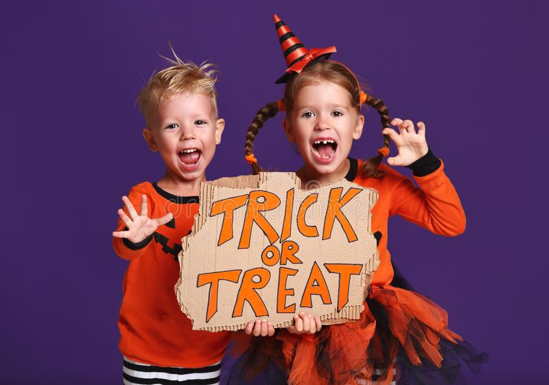 Happy Halloween! cheerful children in costume with pumpkins on v. Happy Halloween! cheerful children in costume with pumpkins on a violet purple background royalty free stock photography