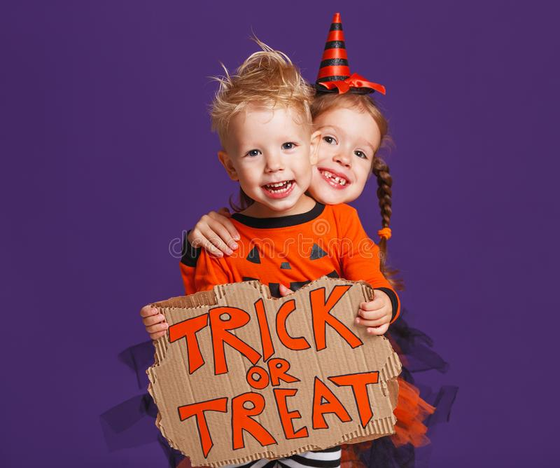 Happy Halloween! cheerful children in costume with pumpkins on v. Happy Halloween! cheerful children in costume with pumpkins on a violet purple background stock images