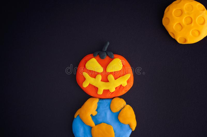 Happy Halloween. Childlike Halloween Art. The Moon, Earth and Pumpkin are made out of modeling clay stock photography