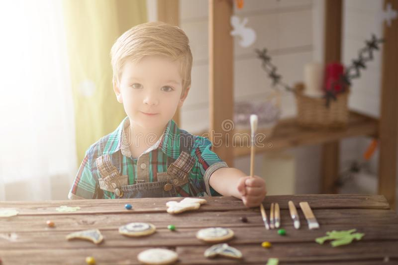 Happy Halloween. Children celebrate Halloween at home. Family trick or treating. Cute funny happy boy covering cookies for Hallowe. En cookies at home royalty free stock photo