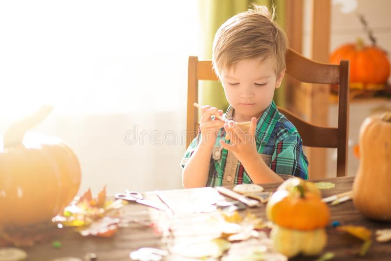 Happy Halloween. Children celebrate Halloween at home. Family trick or treating. Cute funny happy boy covering cookies for Hallowe. En cookies at home stock photo