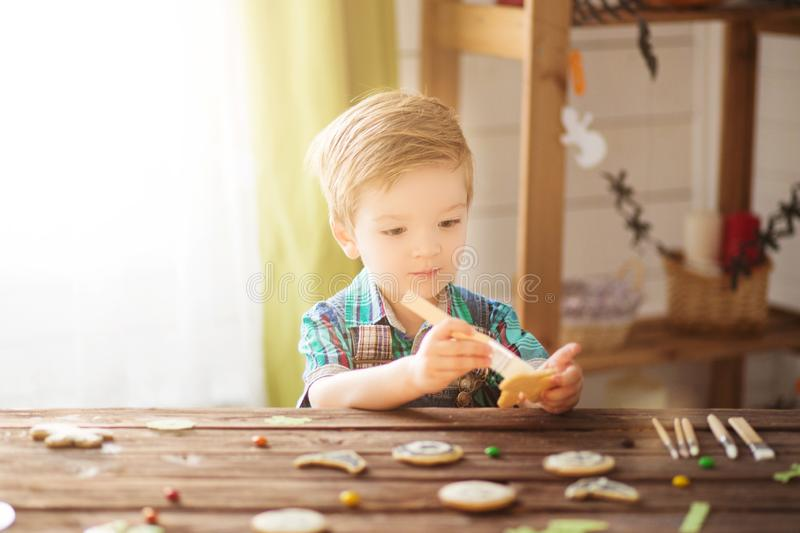 Happy Halloween. Children celebrate Halloween at home. Family trick or treating. Cute funny happy boy covering cookies for Hallowe. En cookies at home royalty free stock photos