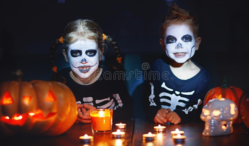 Happy Halloween! children in costume of skeletons with pumpkins. And candles in the dark royalty free stock photography