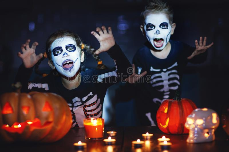 Happy Halloween! children in costume of skeletons with pumpkins. And candles in the dark royalty free stock image