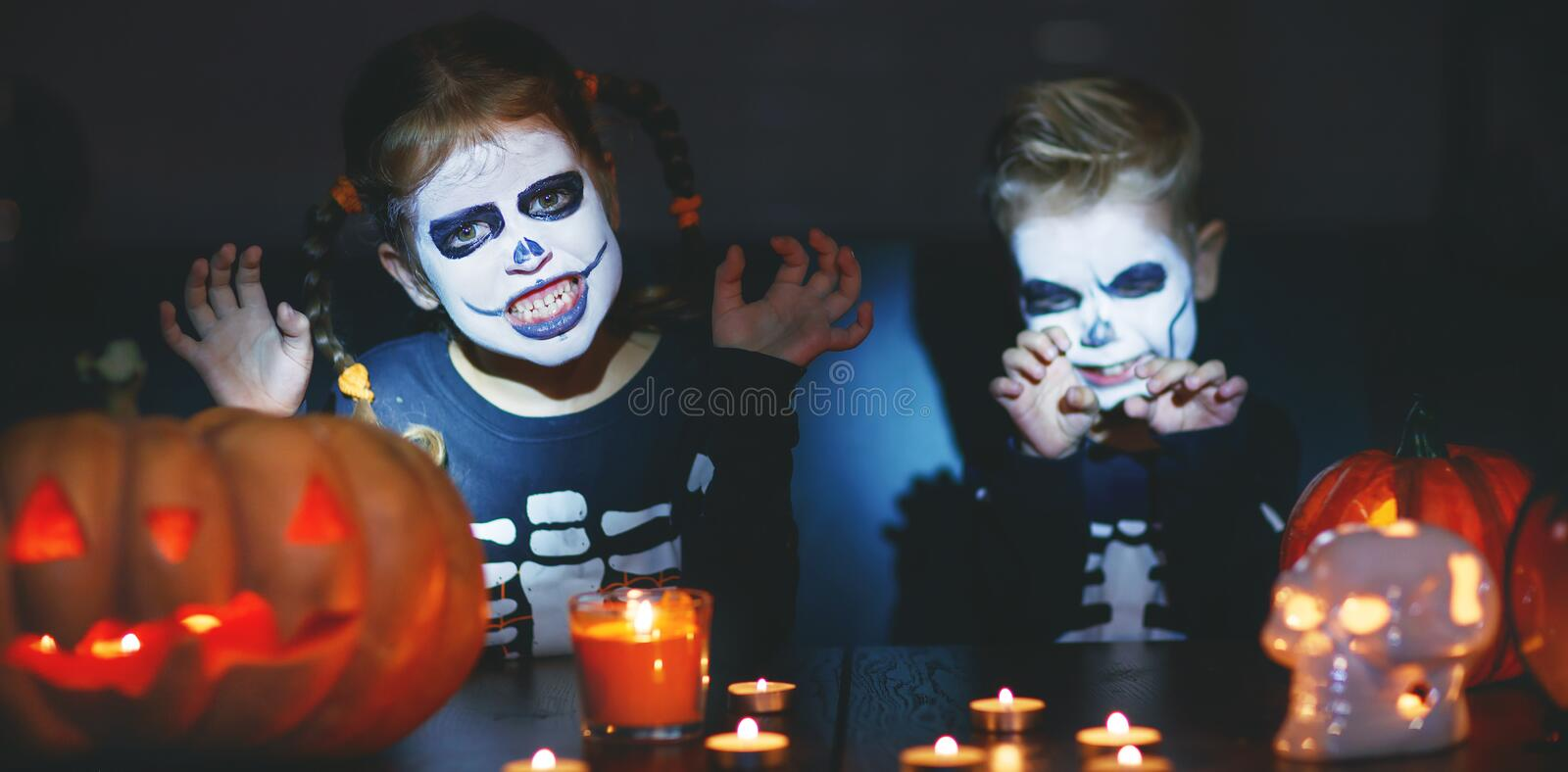 Happy Halloween! children in costume of skeletons with pumpkins. And candles in the dark stock photos