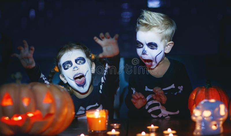 Happy Halloween! children in costume of skeletons with pumpkins. And candles in the dark stock photography