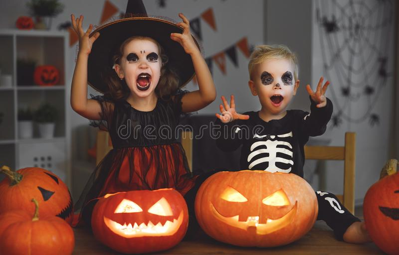 Happy Halloween! children in costume of witch and skeletons with. Pumpkins and candles in the dark royalty free stock photos