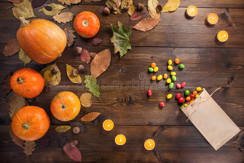 Happy Halloween! The concept of the autumn festival. Small orange pumpkins with dry leaves lie on a brown wooden background, next to the scattered candy and stock photos