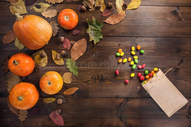 Happy Halloween! The concept of the autumn festival. Small orange pumpkins with dry leaves lie on a brown wooden background, next to the scattered colored royalty free stock photos