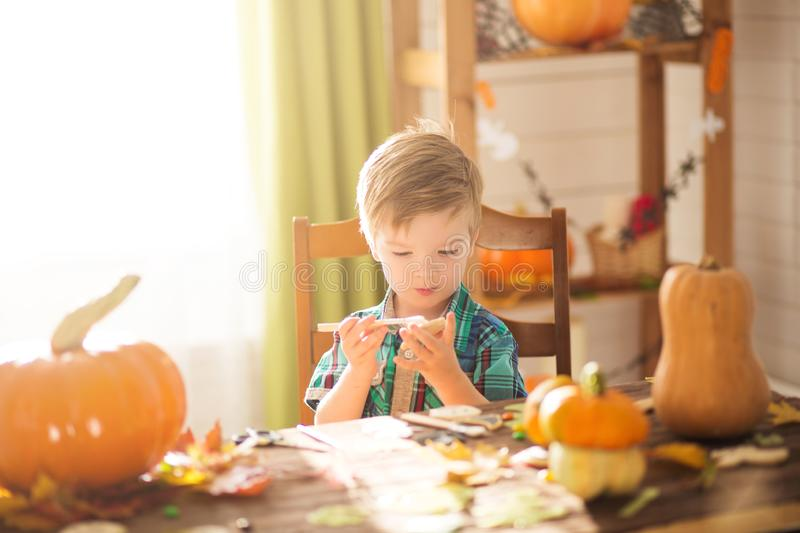 Happy Halloween concept. Cute little happy boy carving a pumpkin and decorated cookies for halloween on a table indoors.  stock photos